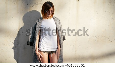 Attractive young girl wearing in a white blank t-shirt and sunglasses posing against a background of a concrete wall in the rays of the setting sun - stock photo