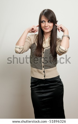 Attractive young girl with fingers in ear not listening - stock photo