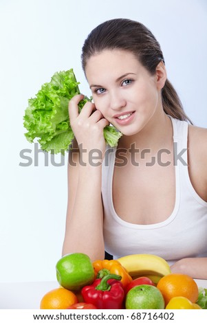 Attractive young girl with fruits and vegetables on white background - stock photo