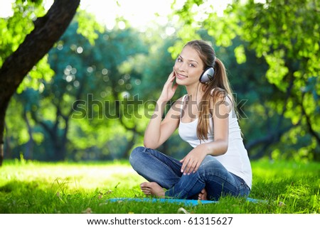 Attractive young girl with headphones in the park