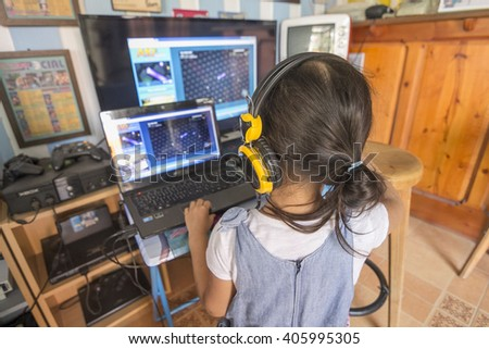 Attractive young girl with long curly brunette hair on a background window playing computer game at home.  - stock photo