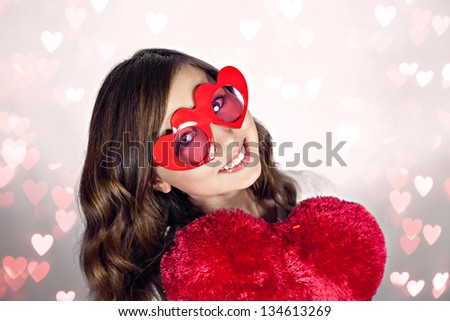 Attractive young girl  with pretty smile and heart shape glasses - stock photo