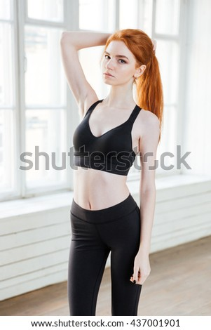 Attractive young girl with red hair wearing sport uniform standing at the gym - stock photo