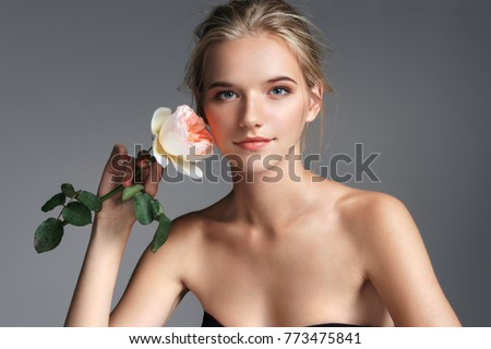 Attractive young girl with rose. Photo of blonde girl with perfect makeup on grey background. Youth and Beauty
