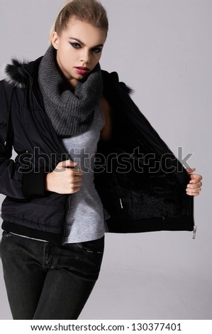 attractive young girl with scarf standing against gray background - stock photo