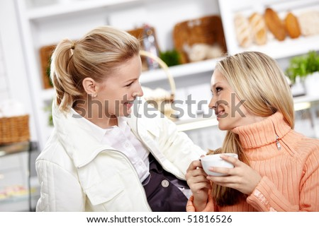 Attractive young girls communicate in cafe - stock photo