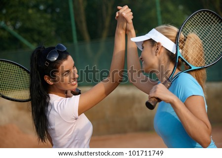 Attractive young girls shaking hands on tennis court, smiling. - stock photo