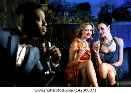Attractive young girls staring at handsome young man in night club. - stock photo