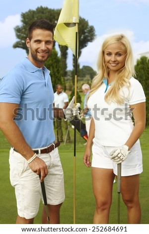 Attractive, young golfers standing on the green, smiling, looking at camera. - stock photo