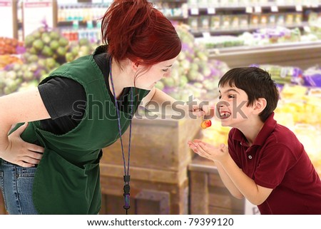 Attractive young grocery clerk sharing fresh cherries with child customer in grocery store. - stock photo