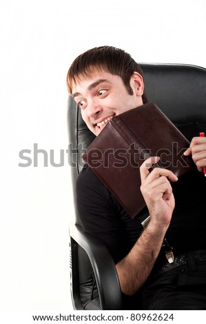 attractive young handsome man belonging to the Caucasoid race isolated, a black turtleneck and pants sitting in a black leather office chair thinks,is holding a daily organizer businessman in office - stock photo