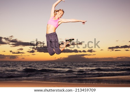 Attractive young happy fitness woman jumping on the beach at sunset - stock photo