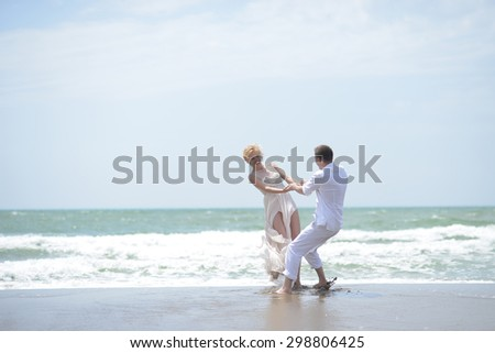 Attractive young happy pair couple of man and woman in white spinning on ocean beach coast on windy weather sunny day outdoor on blue sky background, horizontal picture - stock photo