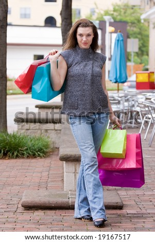 Attractive young happy woman with colorful shopping bags walking in an urban city environment.
