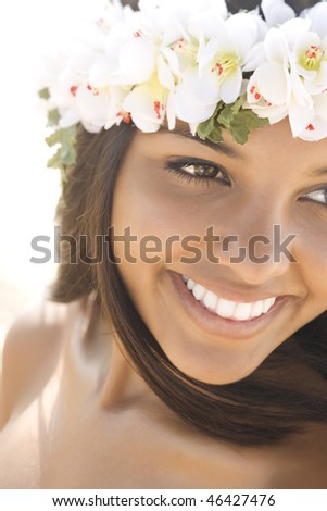 Attractive young Hawaiian woman with a lei on her head smiling. Vertical shot. - stock photo