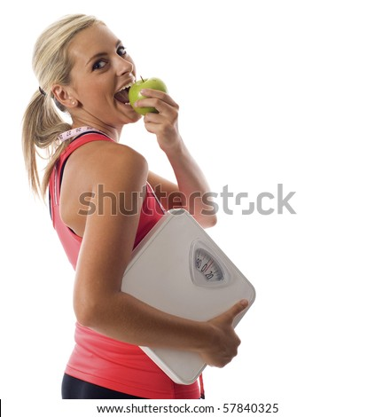 Attractive young healthy woman eating a green apple, carrying measuring tape and a weight scale isolated over white background - stock photo