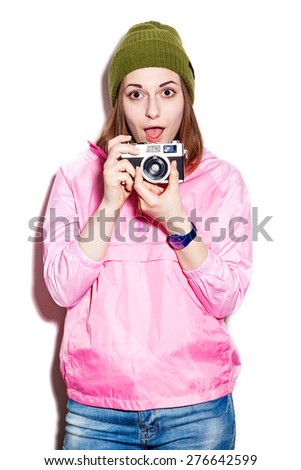 Attractive young hipster girl showing surprise in a pink jacket and green hat. Cheerful girl with a camera. White background not isolated - stock photo