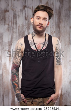 Attractive young hipster is standing near a white wall. He is keeping his arms in pockets. The man is looking at camera with joy - stock photo