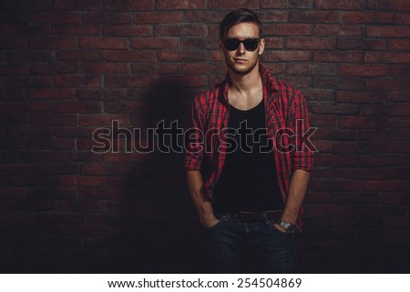 Attractive young hipster smiling and standing against the brick wall with hands in the pockets. - stock photo