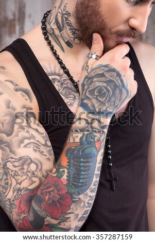 Attractive young hipster with cool tattoo is thinking about something seriously. He is standing and touching his chin pensively - stock photo