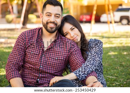 Attractive young Hispanic couple relaxing and cuddling at a park - stock photo