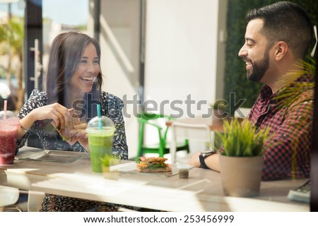 Attractive young Hispanic friends having sandwiches and smoothies for lunch - stock photo