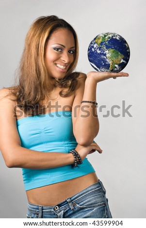 Attractive young Hispanic woman holding the world in her hands.  Earth photo courtesy of NASA. - stock photo