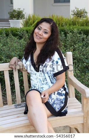 Attractive young Hispanic woman sitting on outdoor bench looking at camera  smiling exuding grace and confidence