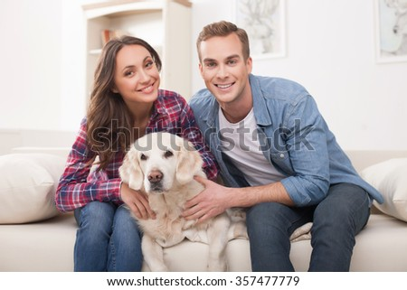 Attractive young husband and wife are sitting on sofa and smiling. They are stroking a dog with love. The family is looking forward happily