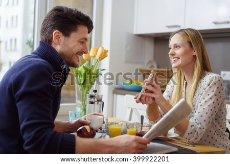 Attractive young husband looking at digital content on the smart phone of wife at kitchen table during breakfast - stock photo