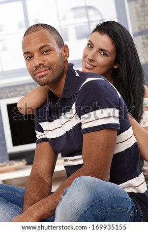 Attractive young interracial couple sitting, embracing at home, smiling. - stock photo
