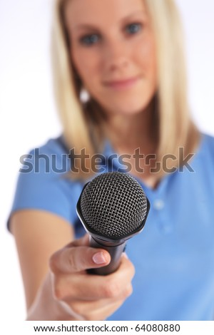 Attractive young interviewer holding a microphone. Selective focus on microphone in foreground. All on white background. - stock photo