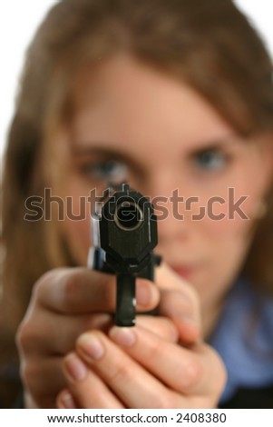 attractive young lady aiming handgun, gun in focus - stock photo