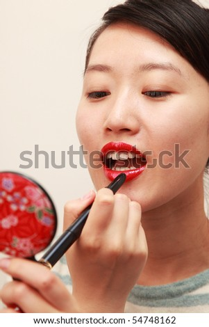 attractive young lady applying lipstick - stock photo