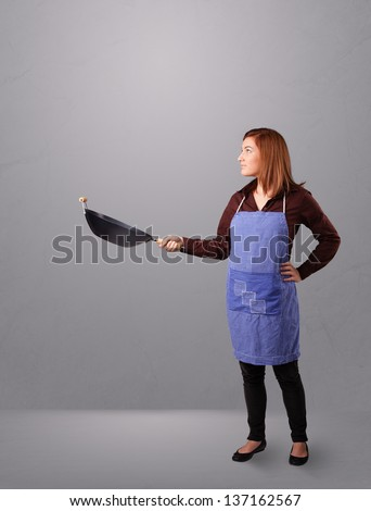 Attractive young lady holding a frying pan