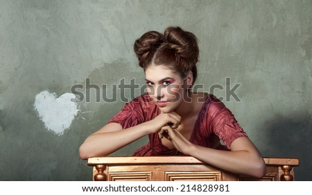 Attractive young lady in pink dress and funny styling posing on gray background. Copy space