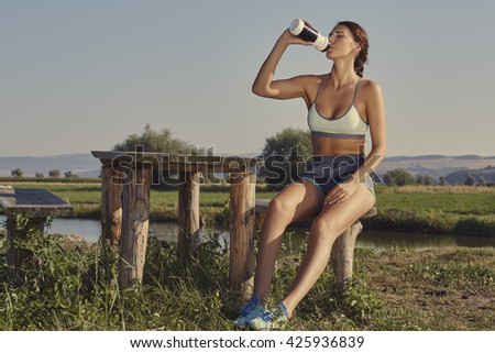 Attractive young lady in summer sportswear drinks water or energizing shake after the morning run while resting on a rustic wooden bench on the bank of a river. - stock photo