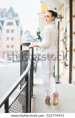 Attractive young lady in white pants and jacket posing outdoors - stock photo