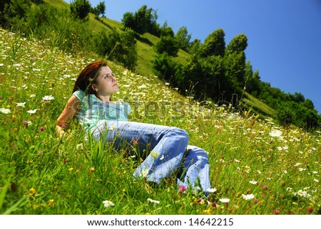 Attractive young lady laying in a field of grass and flowers - stock photo
