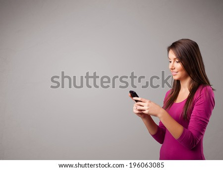 attractive young lady standing and holding a phone with copy space - stock photo