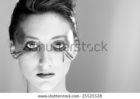 Attractive young lady with extravagant makeup and eyelashes closeup of face