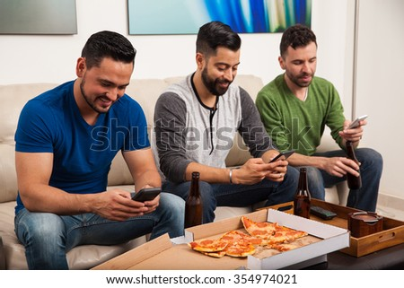 Attractive young Latin men hanging out at home, drinking beer and eating pizza while using their smartphones all at the same time - stock photo