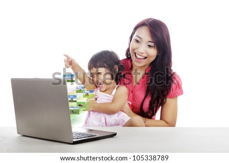 Attractive young little girl and her mother looking at family photos on the laptop - stock photo
