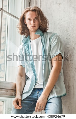 attractive young long-haired caucasian guy in sleeveless shirt, white t-shirt and jeans - stock photo