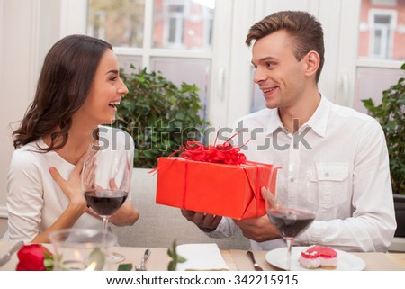 Attractive young loving couple is dating in cafe. The man is giving to the woman a big red box of present. The lady is looking at him with surprise and smiling. They are sitting and drinking wine - stock photo