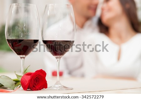 Attractive young loving couple is dating in cafe. They are sitting and smiling. The lovers are embracing and looking at each other with love. Focus on glasses of wine and red rose on table - stock photo