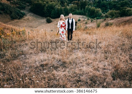 Attractive young loving couple of man in white shirt and with suspenders and gentle girl in dress with red flowers are  standing on sunny outdoor background in the green mountain landscape in sunset