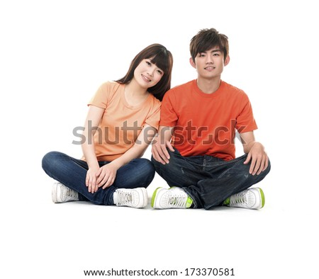 Attractive young loving couple sitting on floor - stock photo