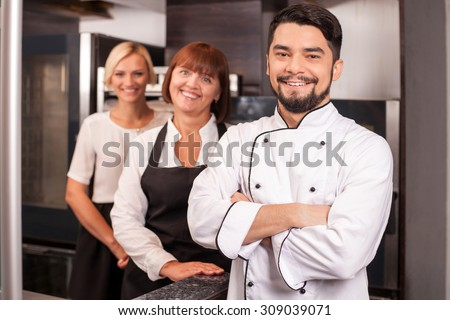 Attractive young male baker and his assistants are standing in kitchen. They are smiling happily. The cooking team is looking at the camera happily - stock photo