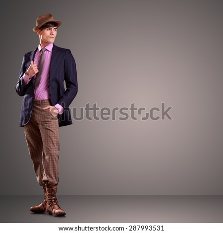 Attractive young male dressed in stylish clothes isolated on gray background - stock photo